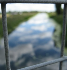 blury river framed by wire fence